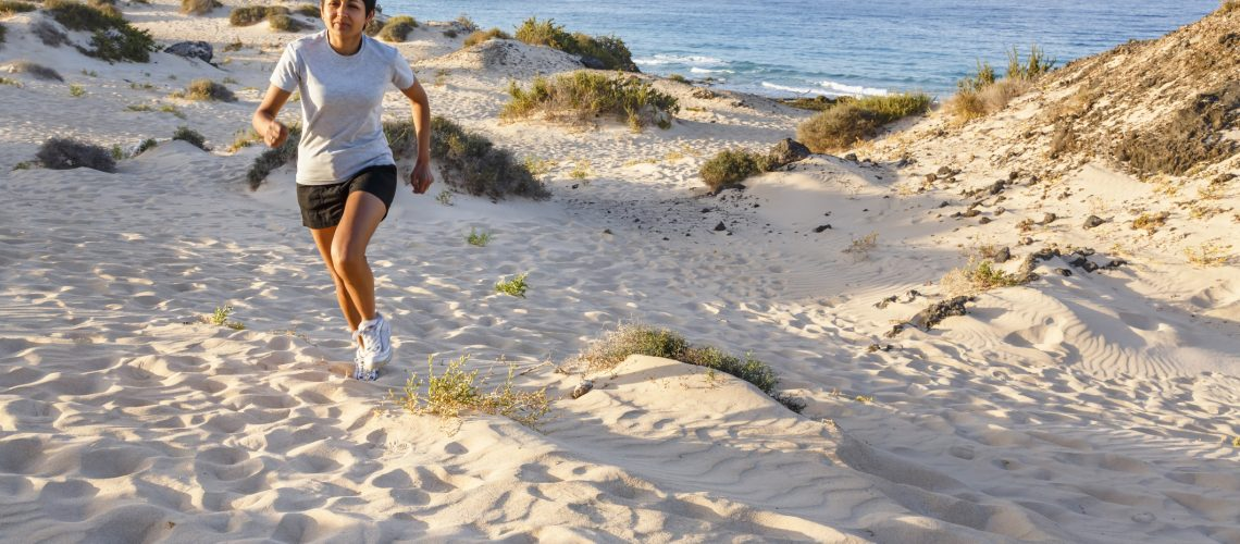 Young Indian female jogging outdoors by the sea